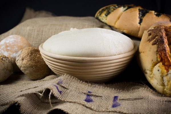Ein Teig im Garkorb mit Brot rings herum
